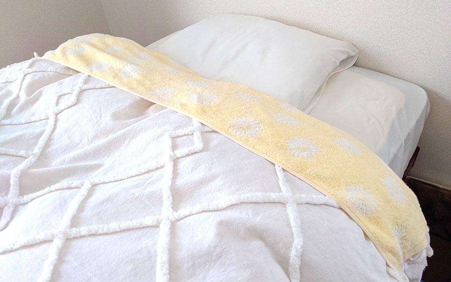 バスタオルを布団の衿元にクリップで付けているところ